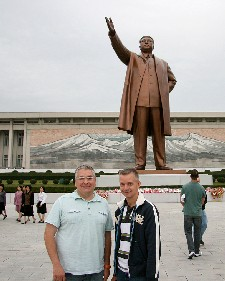 Jim Augusto and Jon Cramer in front of statue of Kim Il Sung in Pyongyang