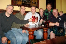 Gary Sannicandro, Chris Hughes, Dave McCormick, John Mather, Scott Anderson, and Bill Smith lift pints at Cumberland Pub in Edinburgh