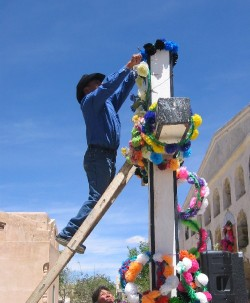 Man decorate large cross on the La Quiaca cemetery