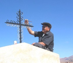 Man paints cross on family grave in preparation of All Souls` Day