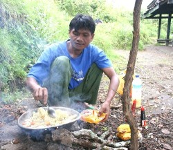 A local guide prepares a meal for a 2-day hiking trek on Lombok