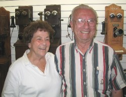 Billie Nell and Charles Hall in front of a collection of vintage telephones