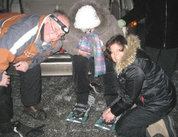 Husband Paul Quirnbach and Mary Kae helping mother Barbara don her snowshoes