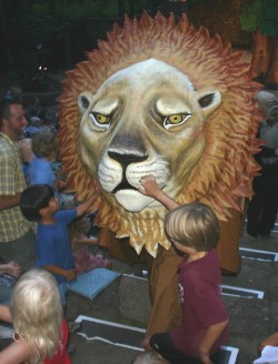 Children touch the lion during the traditional walk thorugh the audience