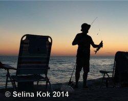 A fisherman fades into a silhouette