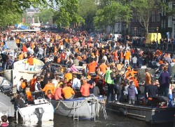 The Prinsengracht canal is jam-packed with boats, most blaring dance music