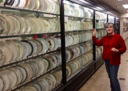 "Guide Phyllis Gorman points to the ""Great Wall of China,"" displaying Replacement's 500 most popular china patterns out of the 265,000 it carries."