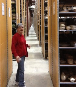 Guide Phyllis Gorman walks down the aisle between rows of warehouse storage on the way to the packing department.