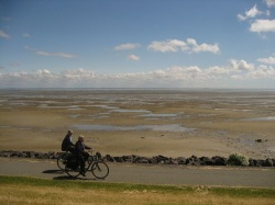 Cyclists on path flanking the dike next to mud flats
